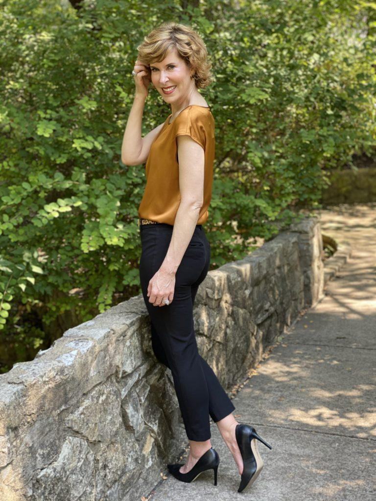 woman wearing lilysilk basic silk tee blak ankle pants leopard print belt black pumps standing on a stone bridge