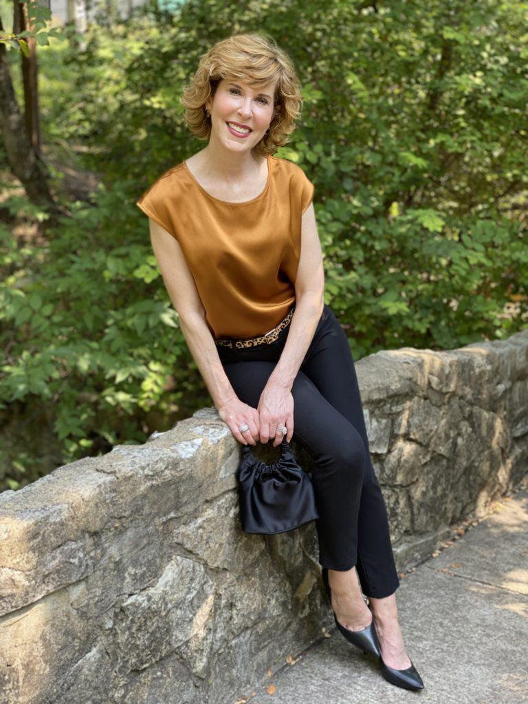 woman wearing lilysilk basic silk tee blak ankle pants leopard print belt black pumps sitting on a stone bridge