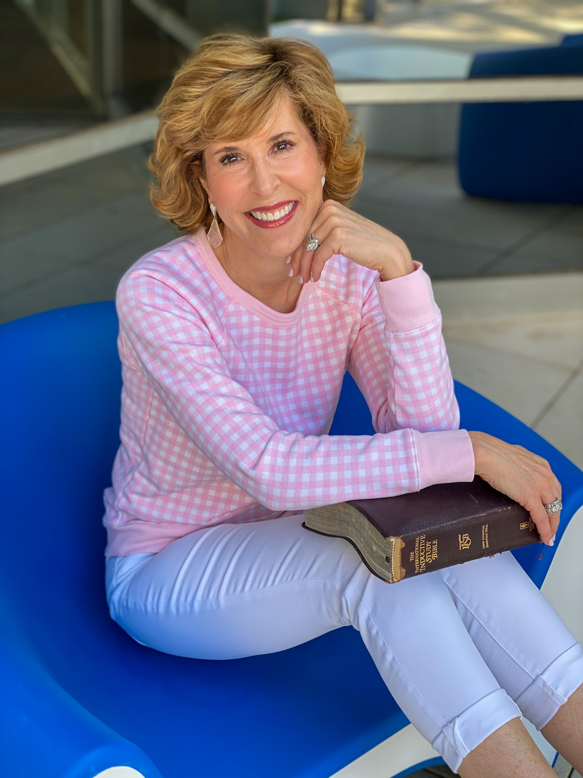woman in pink gingham sweatshirt, white jeans, pink sneakers holding her Bible and sitting in a blue chair
