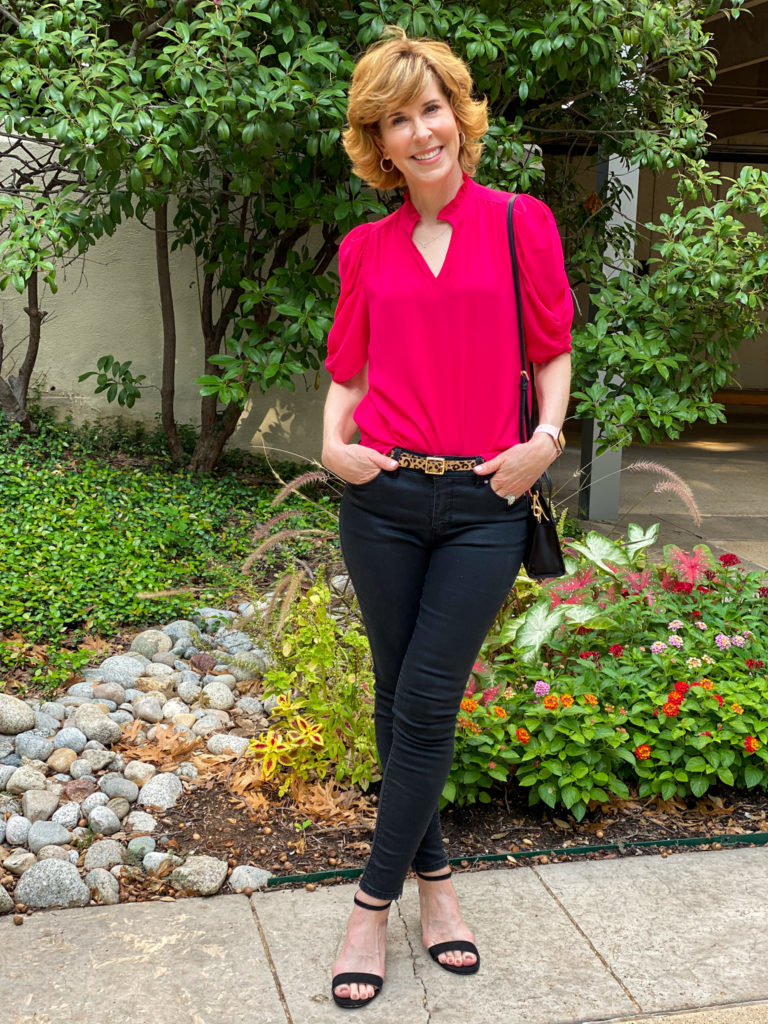 woman in amazon red top and black pants standing in front of flower bed