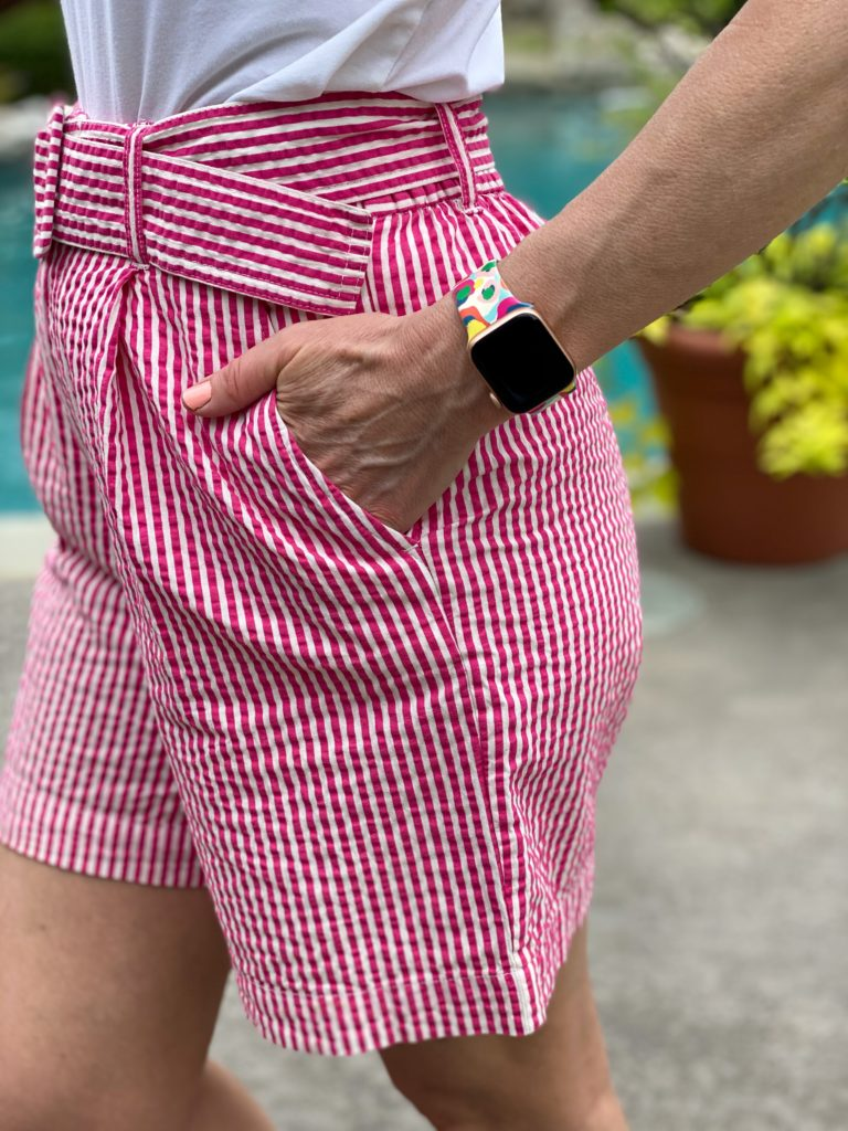 woman wearing pink and white striped seersucker shorts and pink sandals with a colorful apple watch band