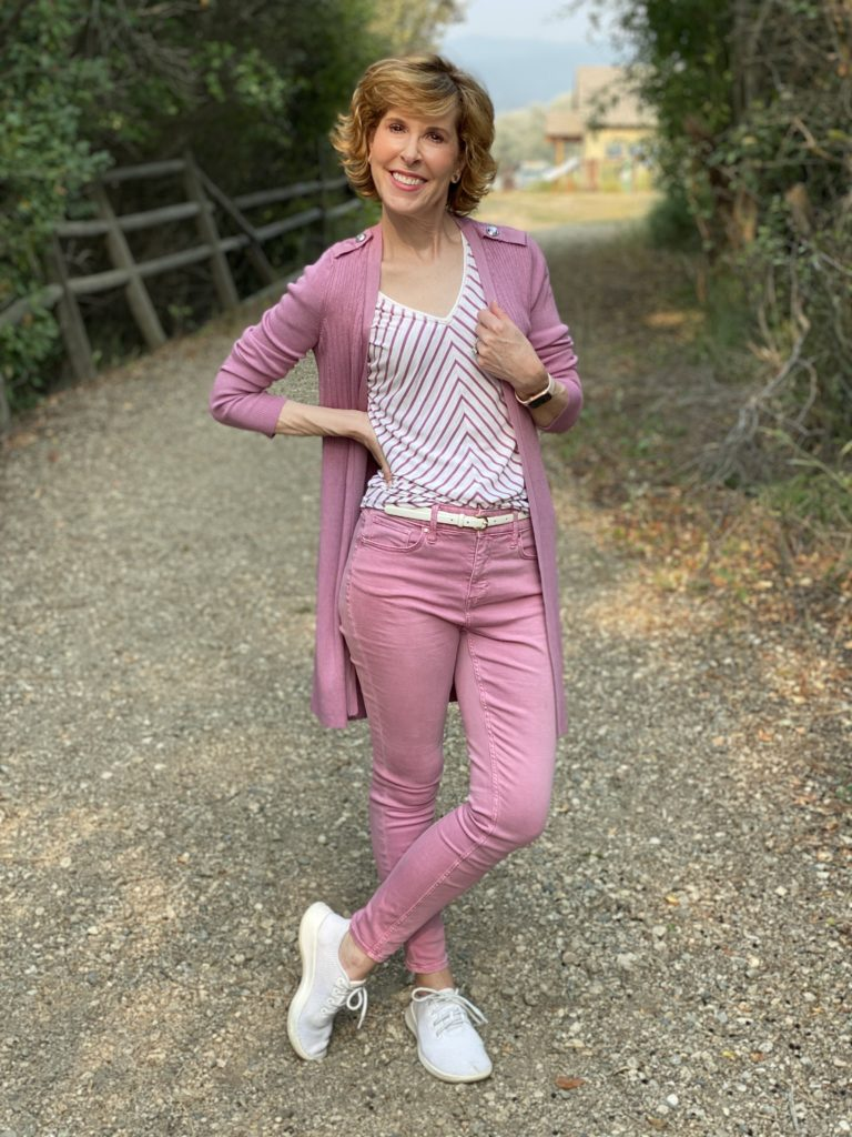 woman wearing whbm pink jeans and matching long duster cardigan with white tennies posing on a road in the country