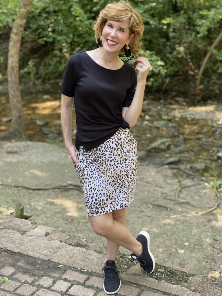 woman wearing chico's black boatneck tee and animal print skort and black tennies posing by a stream