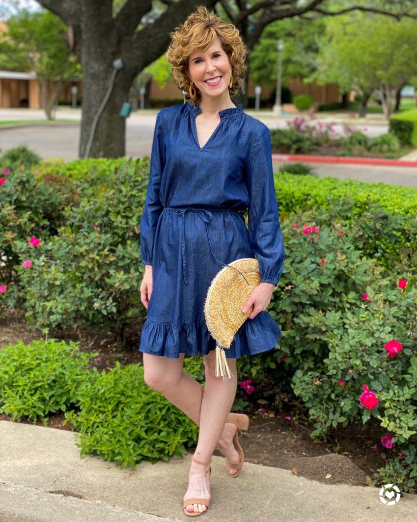woman wearing draper james denim dress posing by flowers
