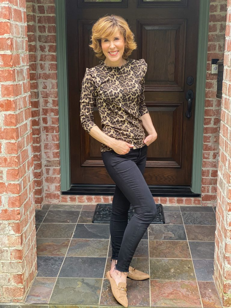 woman standing on porch wearing animal print sweater and black ankle jeans