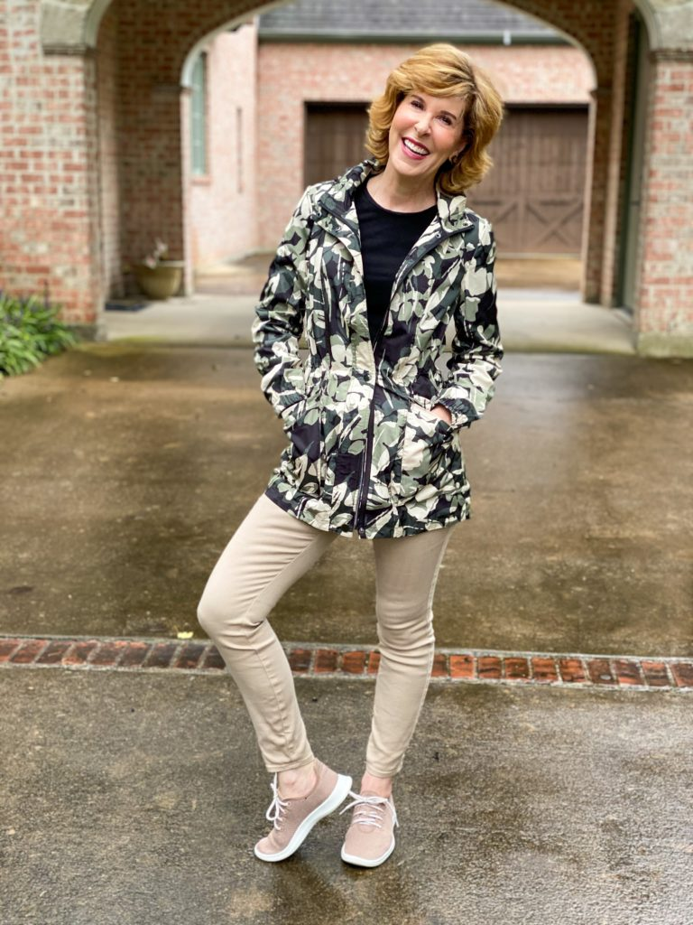 woman standing in driveway wearing Chico's floral camo raincoat and khaki jeans