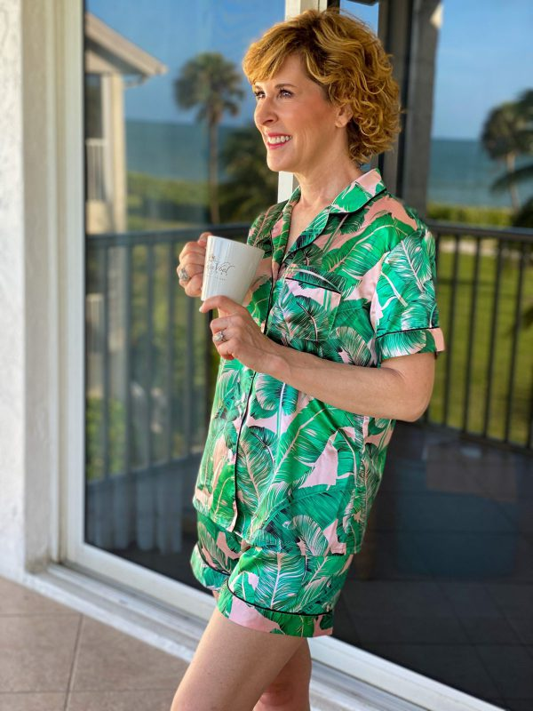 woman standing on lanai wearing silk satin palm print pajamas