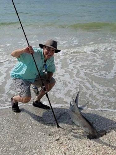 man with hammerhead shark he caught