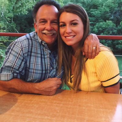 woman dressed in a yellow top posing with her dad