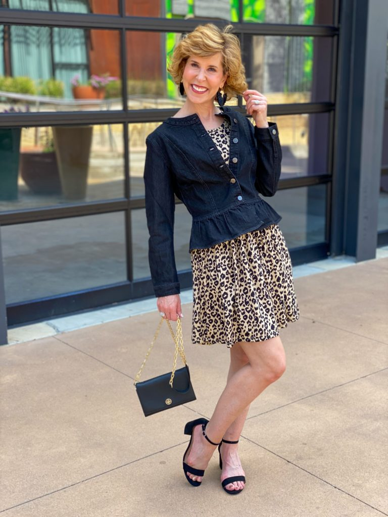 woman over 50 wearing fit and flare leopard print dress and a denim peplum jacket and block heeled sandals from amazon standing in front of a glass paneled wall