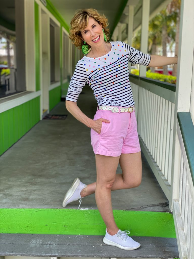 woman wearing boden long sleeve breton tee with pink shorts and beaded palm leaf earrings