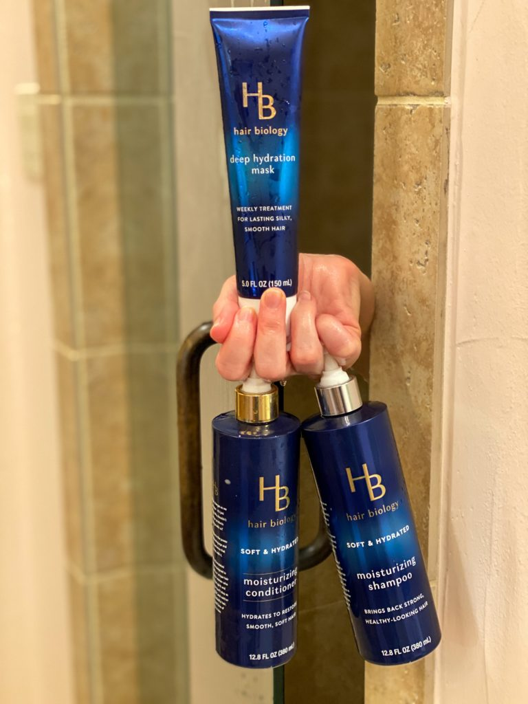 hand holding hair biology hydrating hair care line poking out of shower