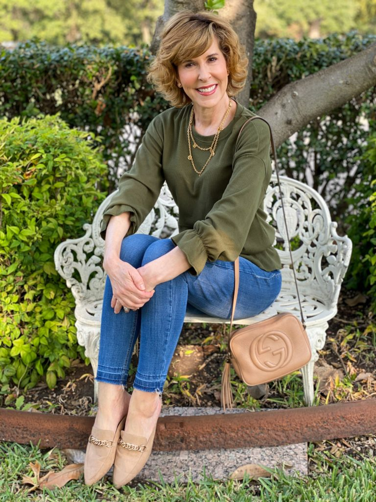 woman wearing green 3/4 sleeve peplum top, jeans, with kell parker chain link mules and gucci tan camera bag
