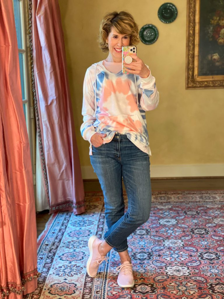 mirror selfie of woman wearing tie-dye pullover top and jeans with pink sneakers