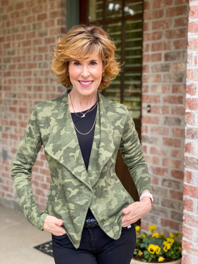 woman over 50 wearing halogen camo knit blazer and black ponte knit jeans and black ruffled booties standing on porch next to pot of pansies