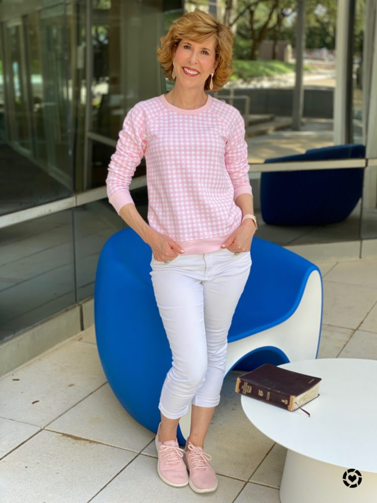 woman wearing draper james pink gingham sweatshirt and white jeans with pink sneakers standing by a blue chair with a bible laying on a white table nearby