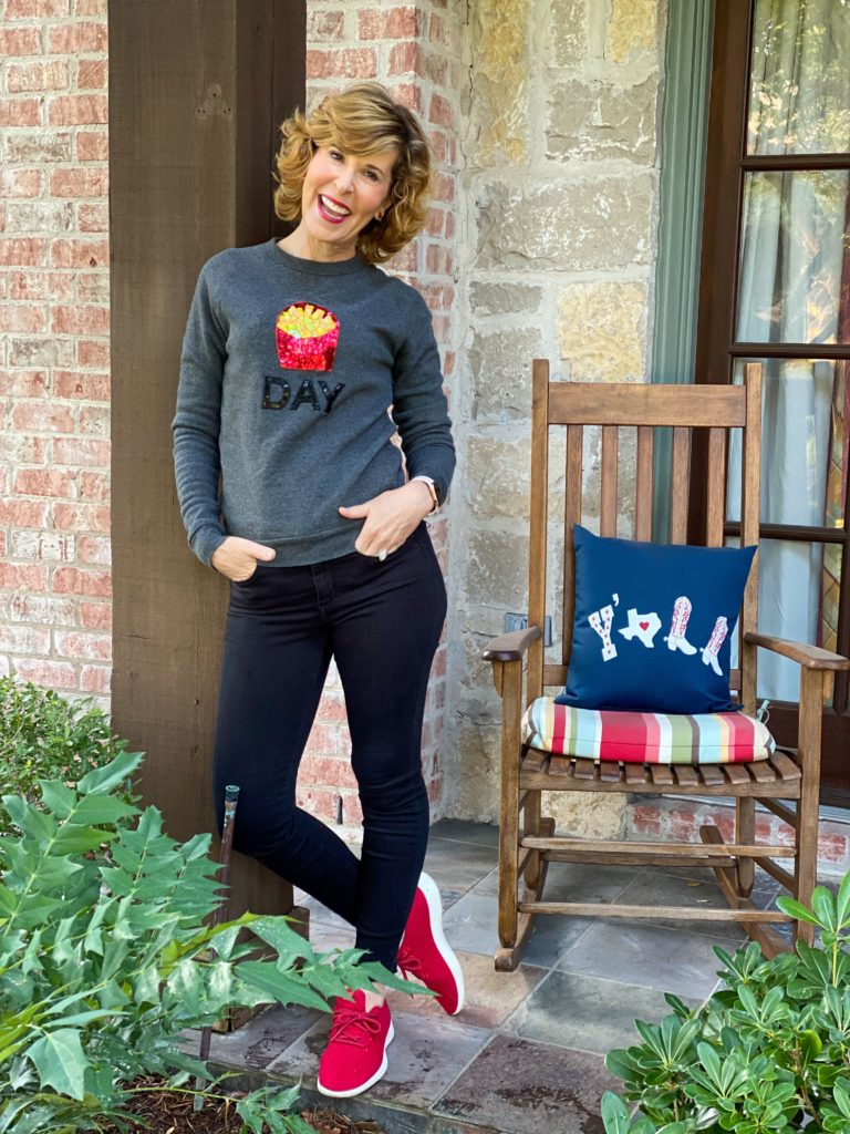 woman over 50 standing on her porch and wearing a spanx bow and drape fry day sweatshirt and black jeans with red sneakers