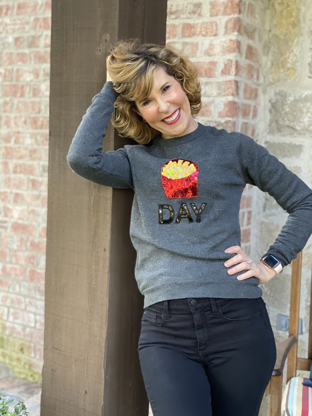 woman over 50 standing on her porch and wearing a spanx bow and drape fry day sweatshirt and black jeans