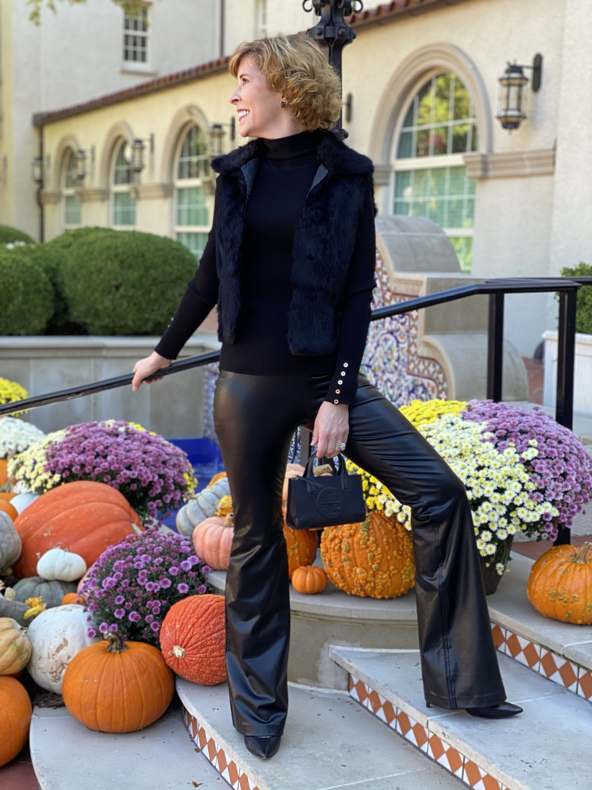woman over 50 wearing a black faux fur vest carrying tory burch micro handbagWalmart Scoop black faux leather pants and