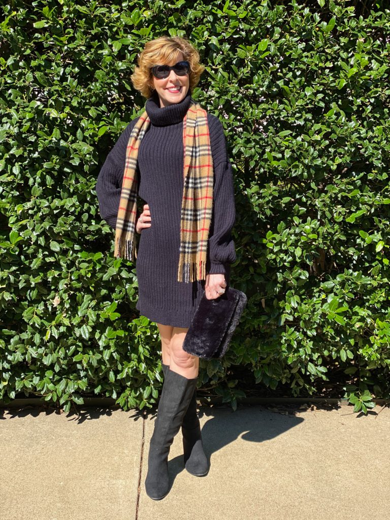 woman over 50 wearing black sweater dress black Target faux suede boots black sunglasses with a cashmere burberry scarf carrying a faux fur clutch purse