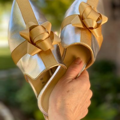 woman holding katy perry bow shoes