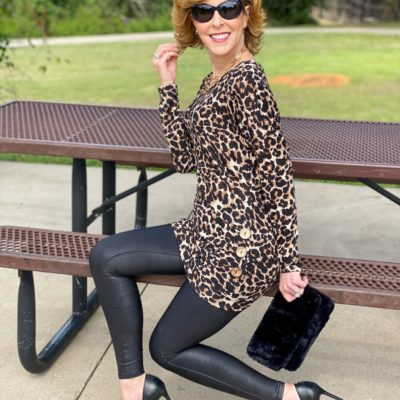 woman wearing amazon leopard side button tunic and spanx faux leather leggings and sam edelman black pumps and amazon sunglasses sitting on the bench of a picnic table