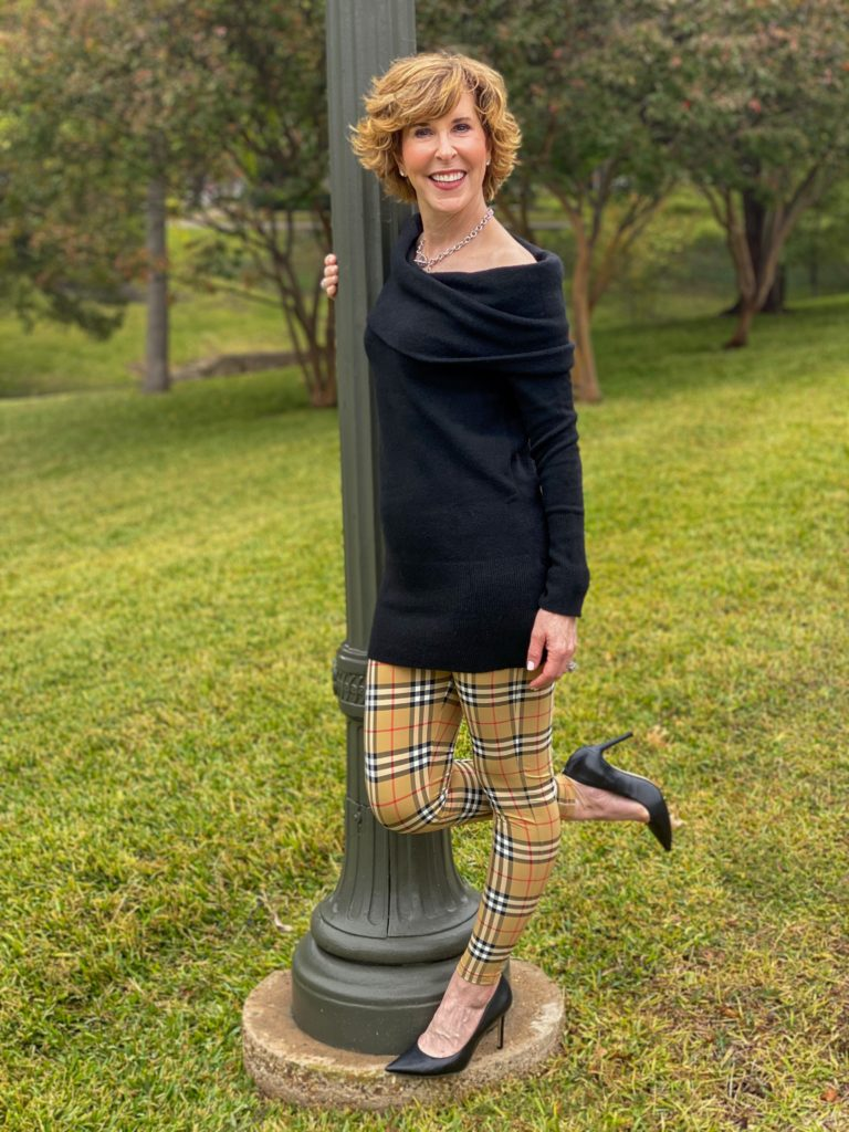 woman over 50 wearing a black off the shoulder sweater and burberry leggings and black pumps standing next to a green lamppost with one leg up in the air