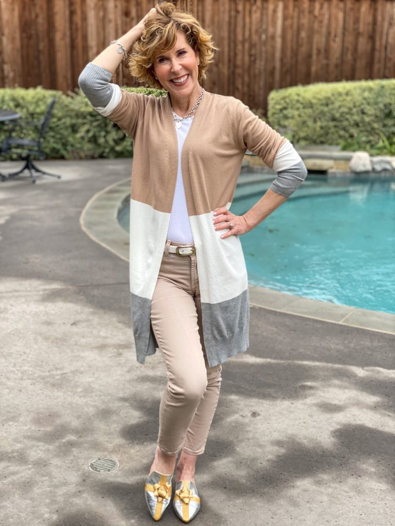 woman over 50 wearing tan jeans, long color block open front cardigan and katy perry bow mules standing in front of a pool