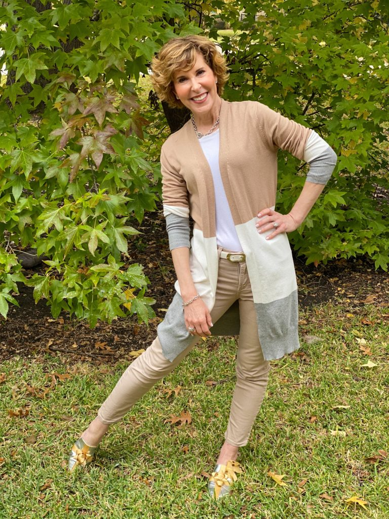 woman over 50 wearing tan jeans, long color block open front cardigan and katy perry bow mules standing in front of bushes
