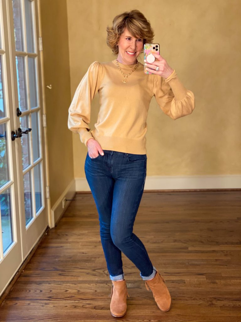 woman over 50 wearing puff sleeve tan sweater and dark blue jeans taking a selfie