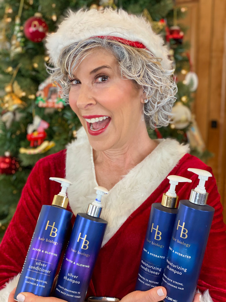 woman dressed as mrs claus holding hair biology haircare produccts