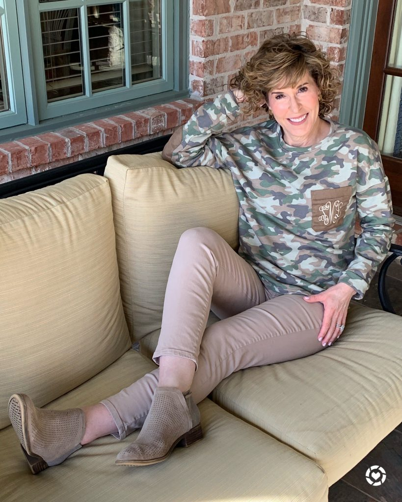 woman lounging on tan outdoor sofa wearing marley lilly monogrammed camo sweatshirt tan khaki jeans and taupe suede booties