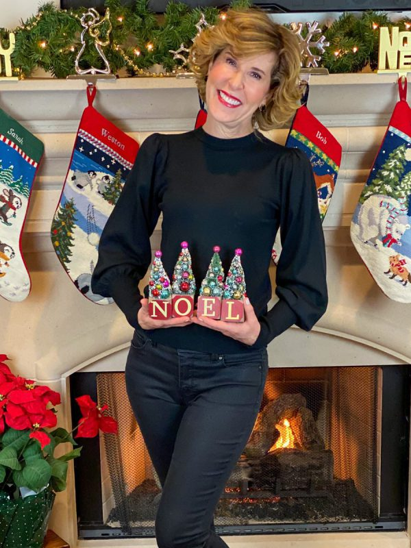woman wearing black sweater and jeans posing in front of a fireplace with stockings hung and a fire inside holding blocks that say NOEL