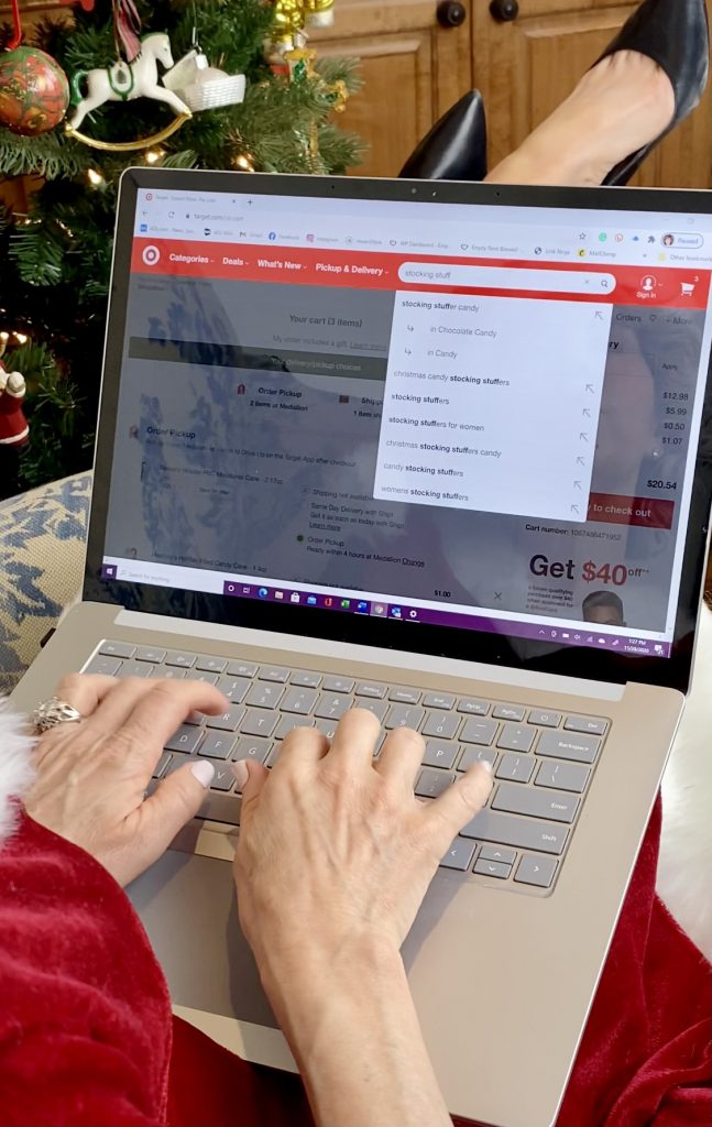 woman safe online shopping on her phone with christmas tree in background
