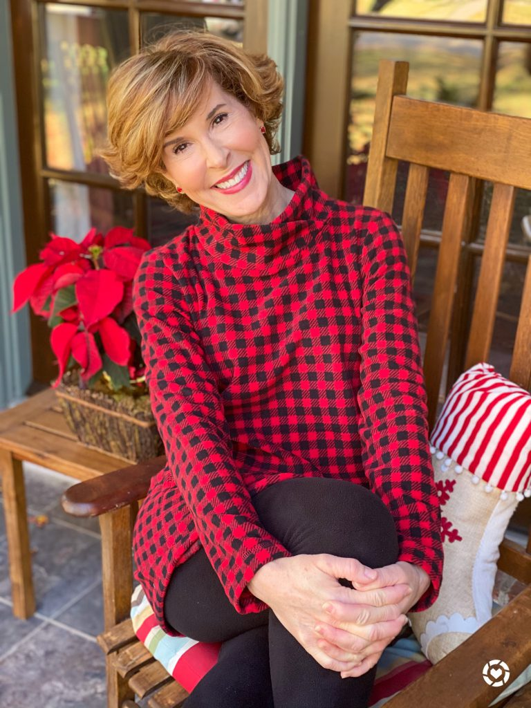 woman wearing red and black buffalo print fleece tunic and black fleece leggings sitting on a rocking chair on her front porch