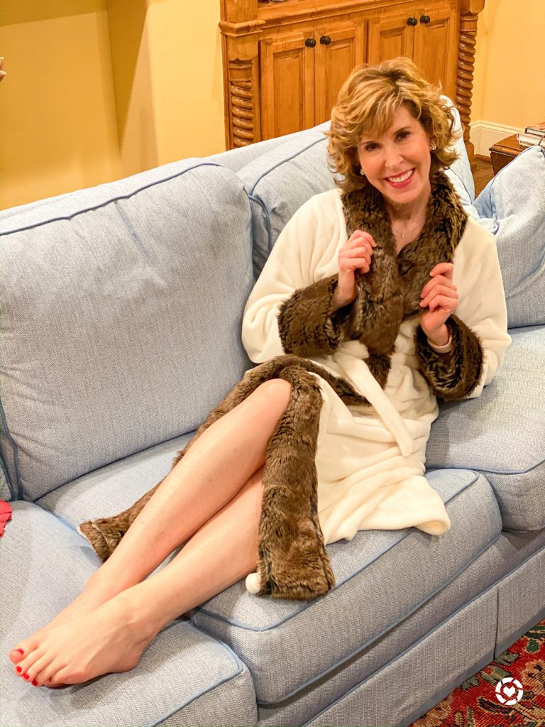 woman wearing a white robe with faux fur trim laying on a blue sofa