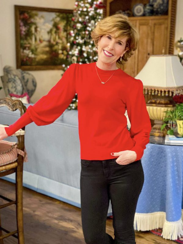woman wearing red sweater and black jeans and black boots standing in her living room