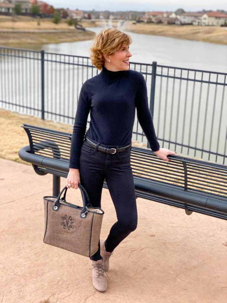 Woman dressed in black turtleneck and black jeans carrying Marley Lilly Monogrammed Charlotte Handbag and wearing marley lilly monogrammed bootiesMarley Lilly Monogrammed Charlotte Handbag