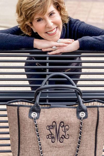woman wearing black turtleneck leaning over a bench with marleylilly's charlotte handbag in front of her sitting on a bench