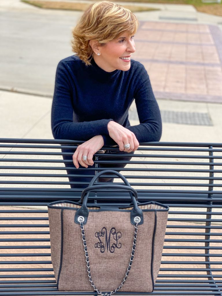 Woman leaning over a park bench with Marley Lilly Monogrammed Charlotte Handbag sitting on the bench in front of her