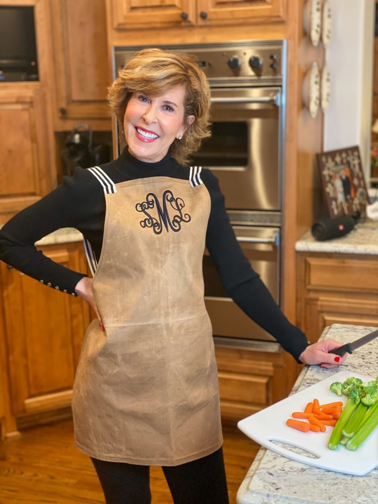 woman over 50 standing in kitchen wearing brown and black marley lilly monogrammed apron