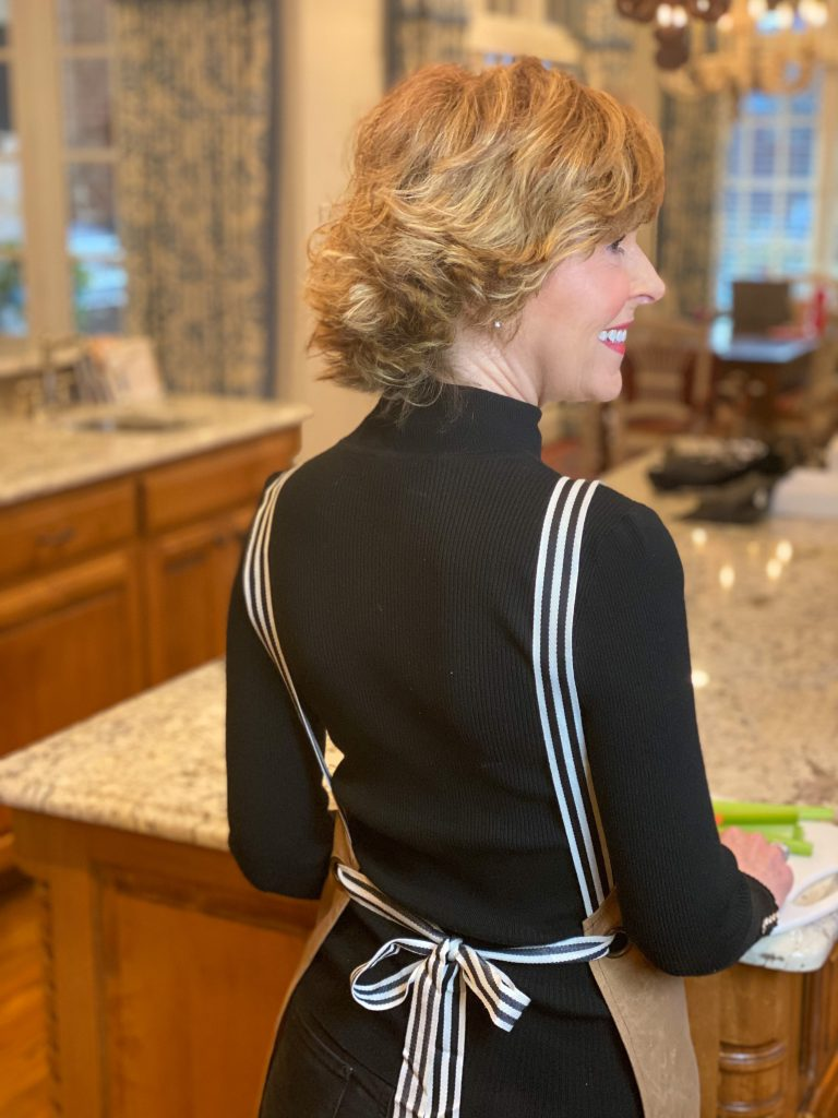 back of woman over 50 standing in kitchen wearing brown and black marley lilly monogrammed apron