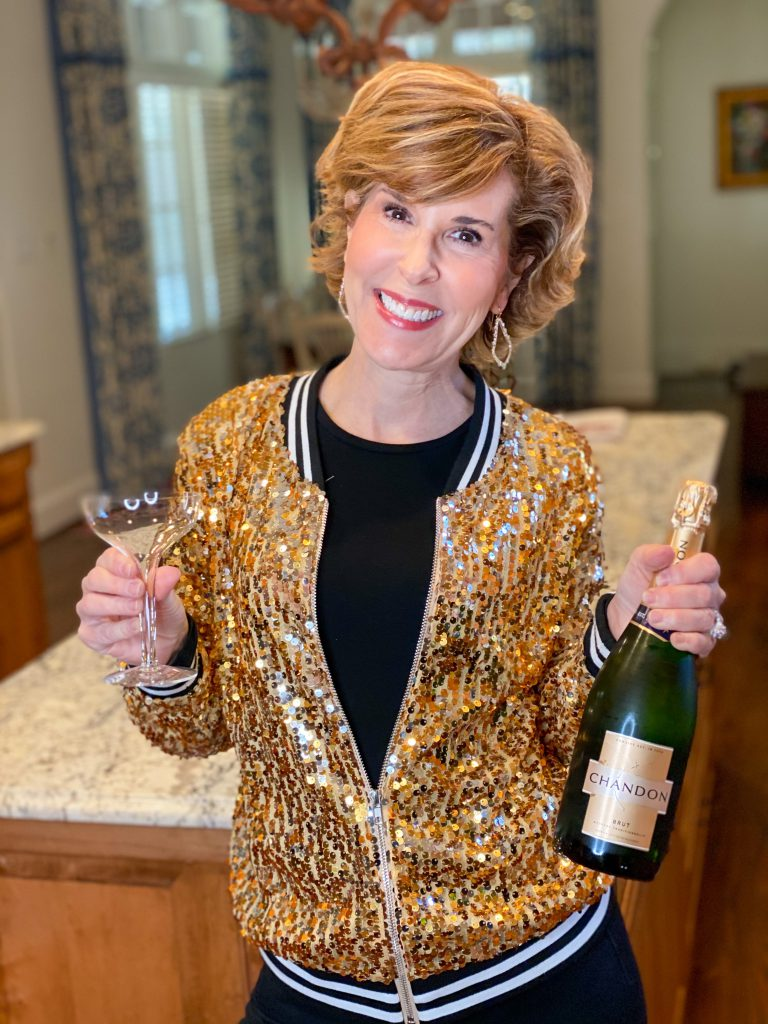 woman wearing gold sequin bomber jacket holding a bottle of champagne and a champagne glass standing in her kitchen