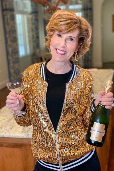 woman celebrating nye at home wearing gold sequin bomber jacket holding a bottle of champagne and a champagne glass standing in her kitchen