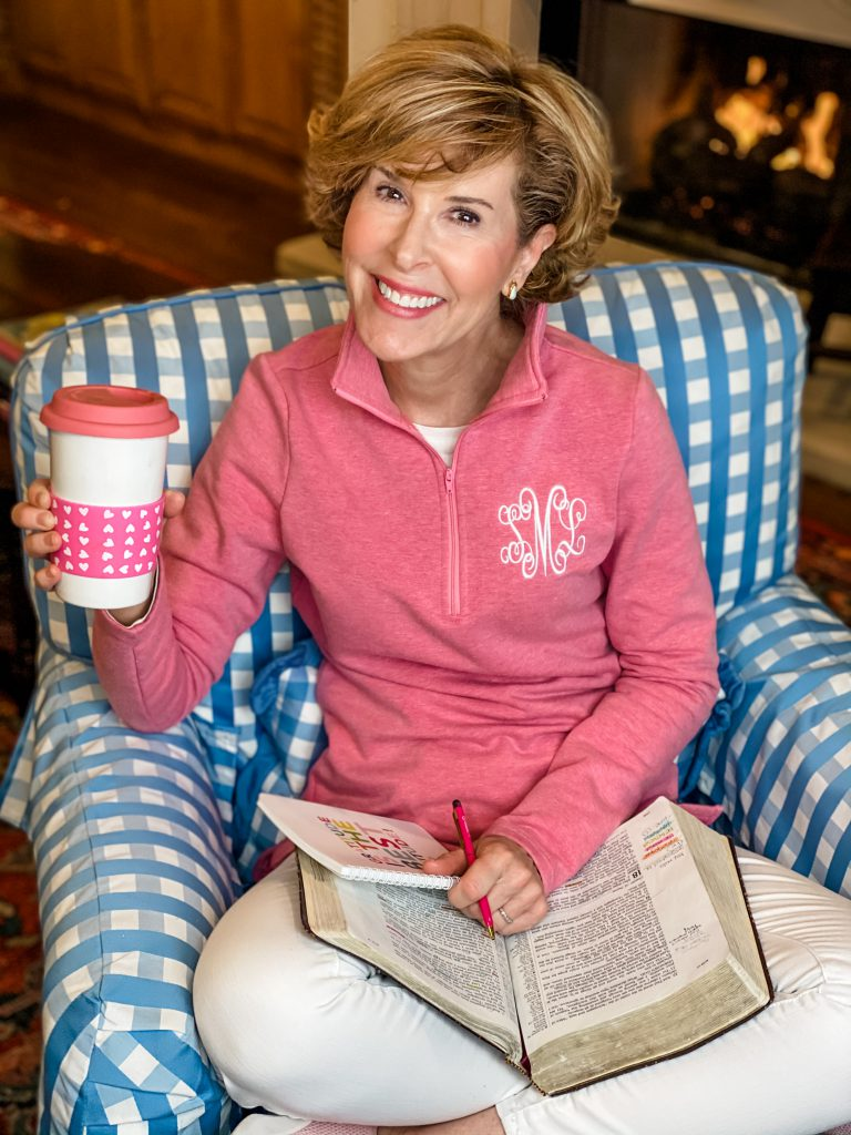 woman sitting in a blue and white gingham chair dressed in a pink monogrammed pullover and white jeans holding a pink and white coffee cup and with a bible and a journal in her lap praying for her adult children