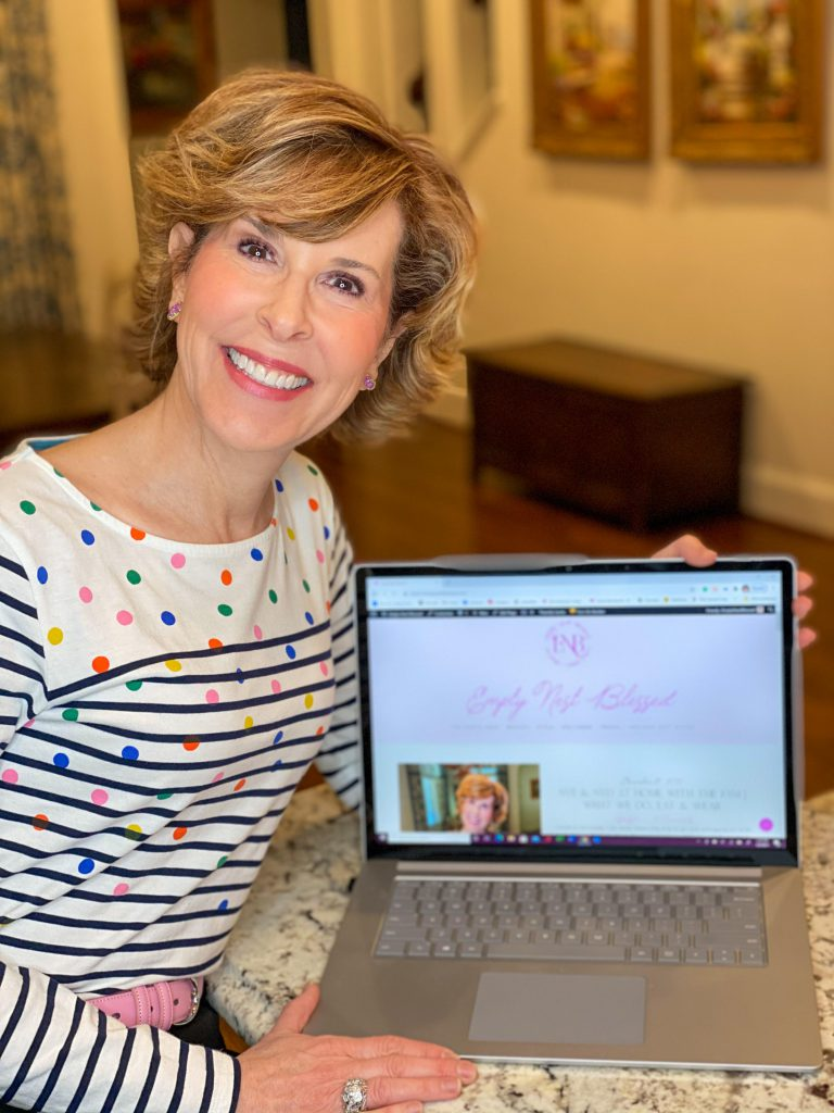 woman over 50 dressed in boden multi colored polka dot and striped Breton shirt sitting next to a computer displaying new empty nest blessed website