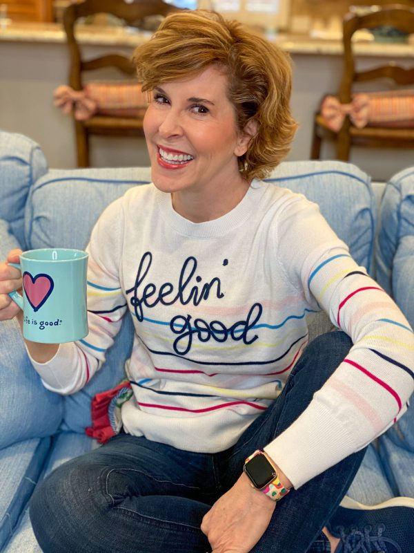 woman wearing walmart feelin' good striped time and tru sweater sitting on a blue sofa holdng a coffee cup talking about skin care over 50