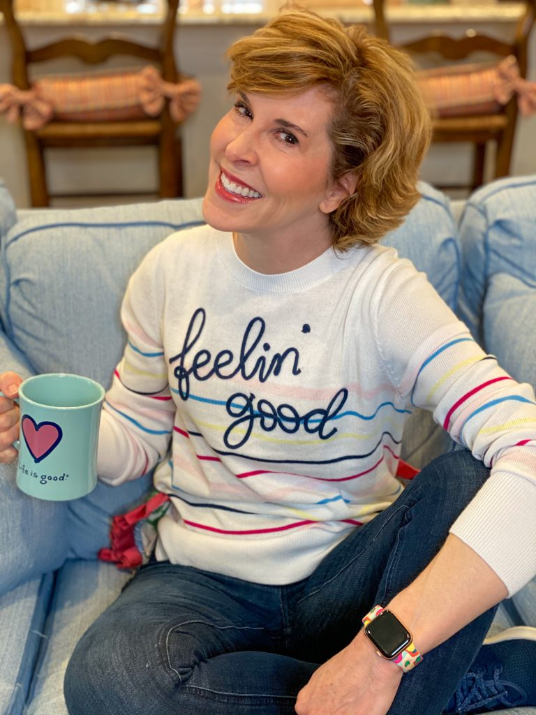 woman wearing walmart feelin' good striped sweater sitting on a sofa holidng a coffee cup talking about skin care over 50
