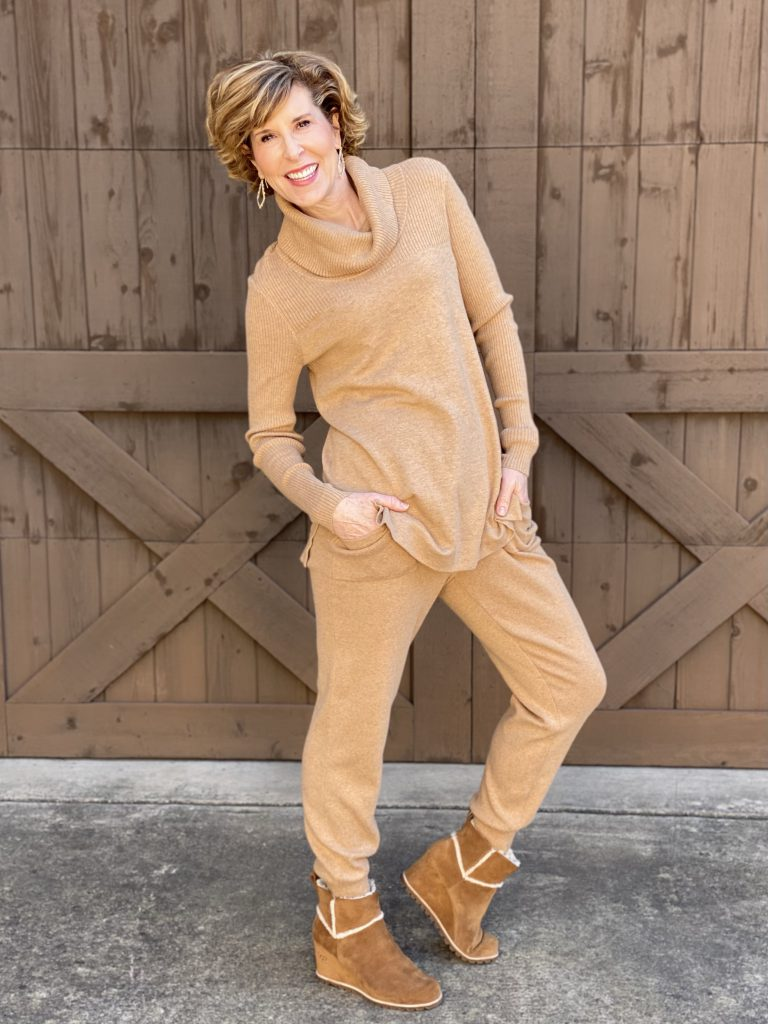 woman wearing chico's cashmere blend joggers and cowl neck tunic in caramel posing in front of a wooden garage door and thinking about her 2021 reboot