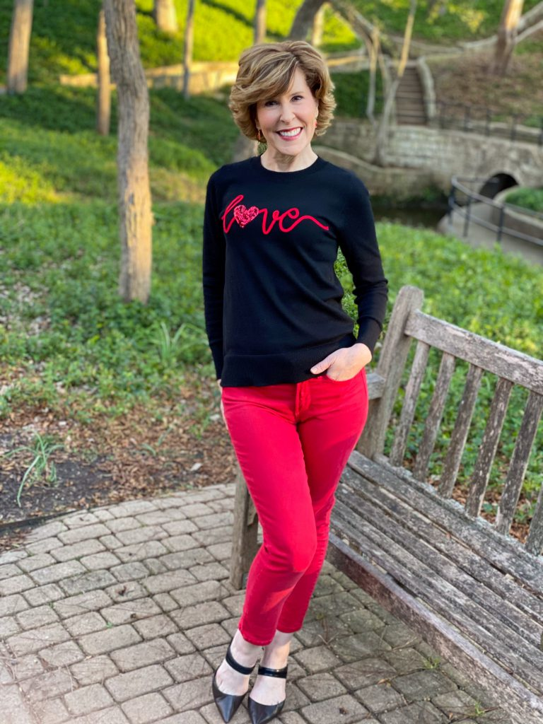 empty nester woman wearing time & tru black with red sequin valentine's sweater red jeans and black heeled pumps standing in a park